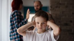 A child covering his ears during his parents' argument