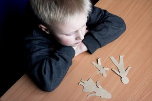 Child looking at cutouts of a family