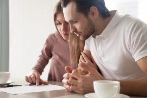 Couple looking at home purchasing paperwork
