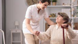 A nurse helping a senior woman