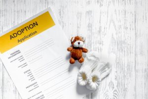 Adoption application near toy on light wooden table