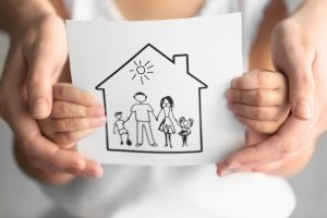 a kid holding a drawing of a family in a home