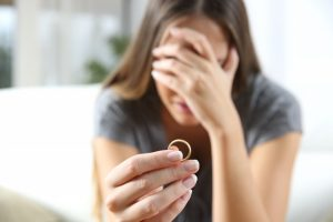 Divorcee holding a ring while crying