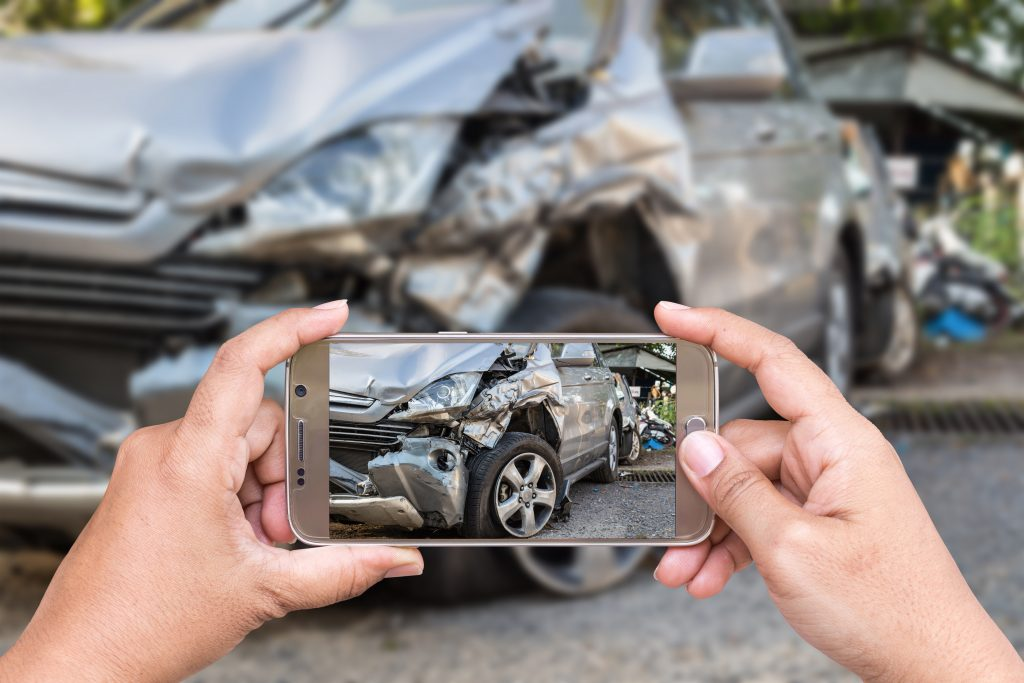 man taking photo of car accident