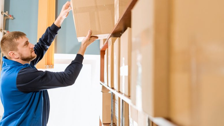 Man putting box on cabinet