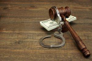 Gavel, dollar cash and handcuffs
