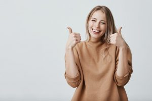 a happy woman showing thumbs up