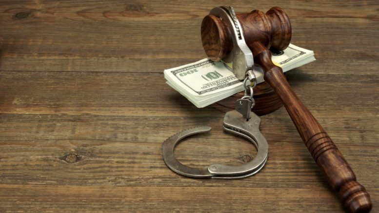 gavel, cash, and handcuffs on table