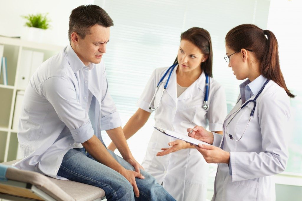 Man reporting ailments to doctor